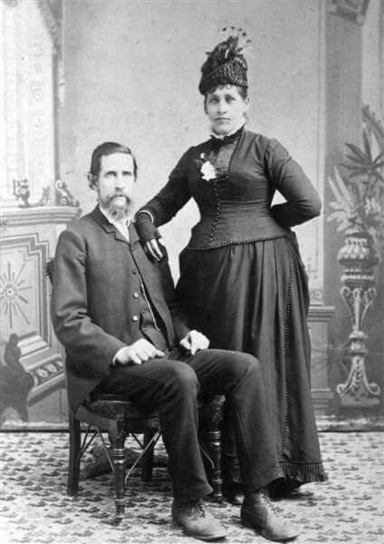 Couple posing for photographer, circa 1880.