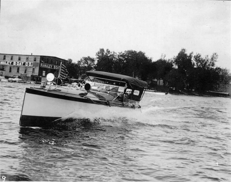 Powered boat on Lake Minnetonka with Ramaley Boat Company in the background, circa 1900.
