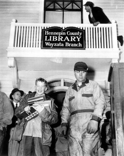 People carrying books from burning library in Village Hall, 1955